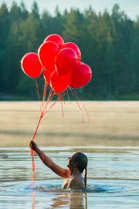 Woman in water holding bunch of red balloonsの写真素材 [FYI03551506]