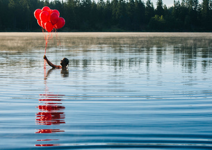 Woman in water holding bunch of red balloonsの写真素材 [FYI03551507]