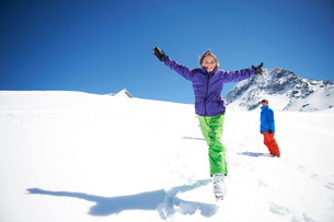 Teenager girl jumping in snow, arms outstretchedの写真素材 [FYI03551661]