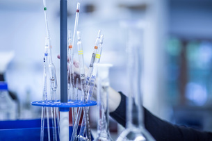 Woman adjusting lab tubes in laboratory, focus on tubesの写真素材 [FYI03551729]