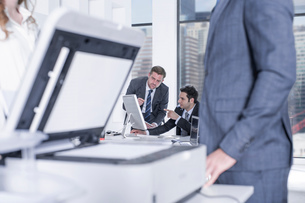 Businessman and businesswomen chatting by photocopier in office, colleagues using computer in backgrの写真素材 [FYI03551815]