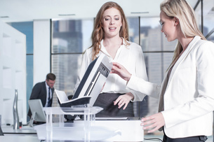 Businesswomen chatting by photocopier in office, colleagues using computer in backgroundの写真素材 [FYI03551817]
