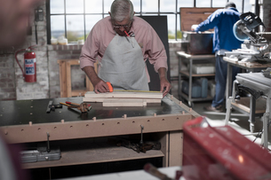 Senior carpenter measuring wood planks in workshopの写真素材 [FYI03551976]