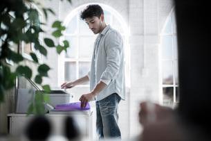 Male designer using fax machine in design studioの写真素材 [FYI03552035]