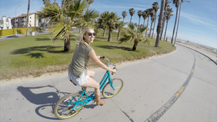 Portrait of young woman cycling at Venice Beach, California, USAの写真素材 [FYI03552107]