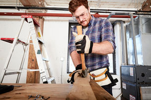 Carpenter in workshop removing nails form timber using hammerの写真素材 [FYI03552173]
