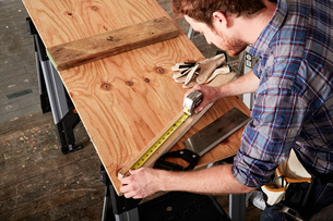 Over shoulder view of carpenter in workshop measuring timberの写真素材 [FYI03552179]