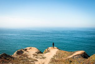 Man looking out over Pacific Ocean by Highway 1, California, USAの写真素材 [FYI03552232]