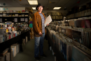 Portrait of mature man in record shop, holding recordsの写真素材 [FYI03552260]