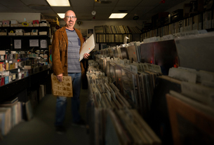 Portrait of mature man in record shop, holding recordsの写真素材 [FYI03552261]
