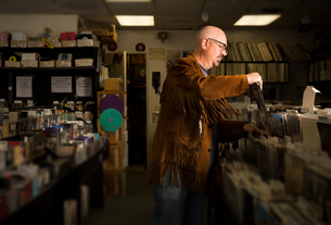 Mature man in record shop, filing recordsの写真素材 [FYI03552263]