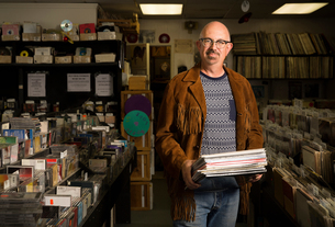 Portrait of mature man in record shop, holding recordsの写真素材 [FYI03552265]