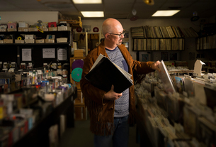 Mature man in record shop, filing recordsの写真素材 [FYI03552266]