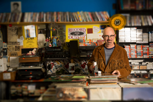 Portrait of mature man in record shop, pricing up records using price gunの写真素材 [FYI03552267]