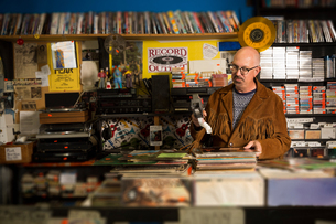 Mature man in record shop, pricing up records using price gunの写真素材 [FYI03552268]