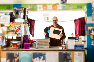Portrait of mature man in record shop, putting record into record sleeveの写真素材 [FYI03552271]