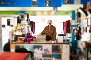 Portrait of mature man in record shop, leaning on stack of recordsの写真素材 [FYI03552272]