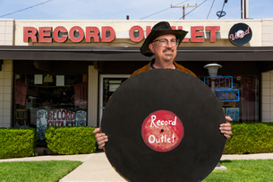 Portrait of mature man outside record shop, holding large imitation recordの写真素材 [FYI03552273]