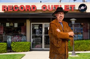 Portrait of mature man outside record shopの写真素材 [FYI03552274]