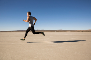 Man training, running on dry lake bed, El Mirage, California, USAの写真素材 [FYI03552278]
