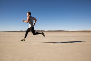Man training, running on dry lake bed, El Mirage, California, USAの写真素材 [FYI03552278]