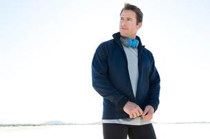 Man training, zipping tracksuit top on dry lake bed, El Mirage, California, USAの写真素材 [FYI03552281]