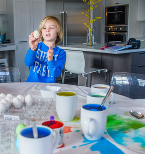 Boy in kitchen decorating eggs for Easterの写真素材 [FYI03552421]