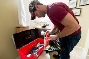 Man selecting spirit level from tool box in bathroomの写真素材 [FYI03552429]
