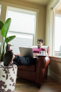 Man on living room armchair with feet up working on laptopの写真素材 [FYI03552435]