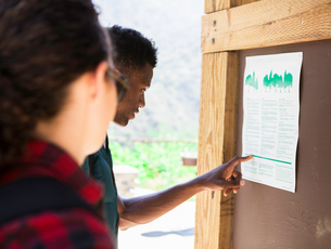 Young female and male hikers pointing at information on notice board, Arcadia, California, USAの写真素材 [FYI03552463]