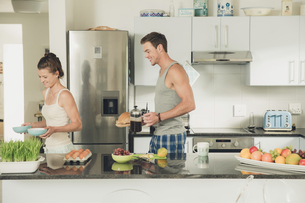 Young couple carrying breakfast from kitchen counterの写真素材 [FYI03552503]