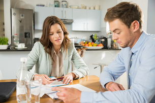 Young couple at kitchen table reading bills and paperworkの写真素材 [FYI03552520]
