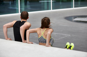 Young woman and man training, doing push ups against wallの写真素材 [FYI03552609]