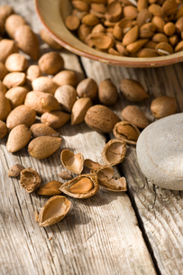 Bowl of almonds (Prunus dulcis) broken and in nutshells on tableの写真素材 [FYI03552643]