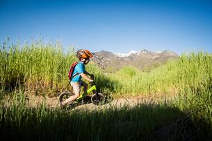 Boy cycling in park, Sandy, Utah, USAの写真素材 [FYI03552661]