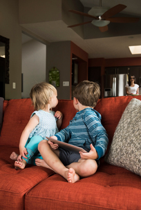 Siblings turning around from digital tablet on sofaの写真素材 [FYI03552672]