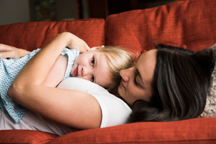 Mother hugging daughter on sofaの写真素材 [FYI03552676]