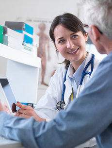 Doctor sharing health information on digital tablet with patient in clinicの写真素材 [FYI03552697]