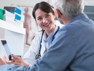 Doctor sharing health information on digital tablet with patient in clinicの写真素材 [FYI03552698]