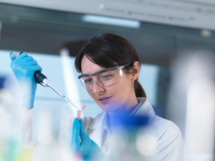 Researcher pipetting DNA sample into eppendorf vial in laboratoryの写真素材 [FYI03552713]