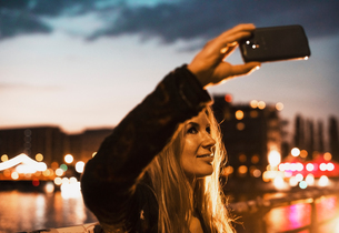 Young woman by waterfront, taking selfie with smartphoneの写真素材 [FYI03552890]