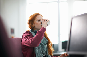 Young female college student at computer desk drinking takeaway coffeeの写真素材 [FYI03552989]