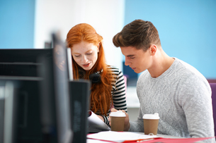 Young female and male college students reading at computer deskの写真素材 [FYI03553008]
