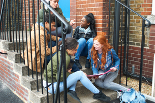 Young adult college student friends chatting and revising on campus stairsの写真素材 [FYI03553054]