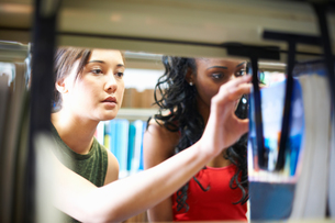 Two young female college students searching library shelvesの写真素材 [FYI03553076]