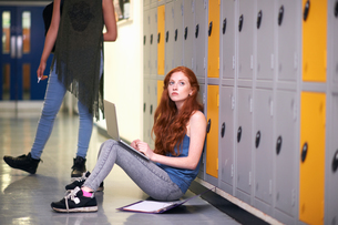 Young female college student sitting on locker room floor gazing whilst revising on laptopの写真素材 [FYI03553086]
