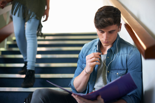 Young male college student sitting on stairway reading fileの写真素材 [FYI03553093]