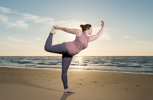 Mature woman practising yoga on a beach at sunset, tree poseの写真素材 [FYI03553113]