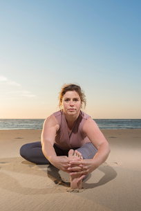 Mature woman practising yoga on a beach at sunset, portrait touching toesの写真素材 [FYI03553116]
