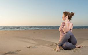 Mature woman practising yoga on a beach at sunset, sitting cross leggedの写真素材 [FYI03553118]